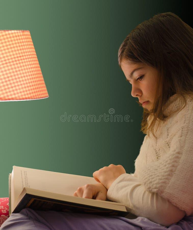Livre de lecture de petite fille sous la lumière de la lampe images libres de droits