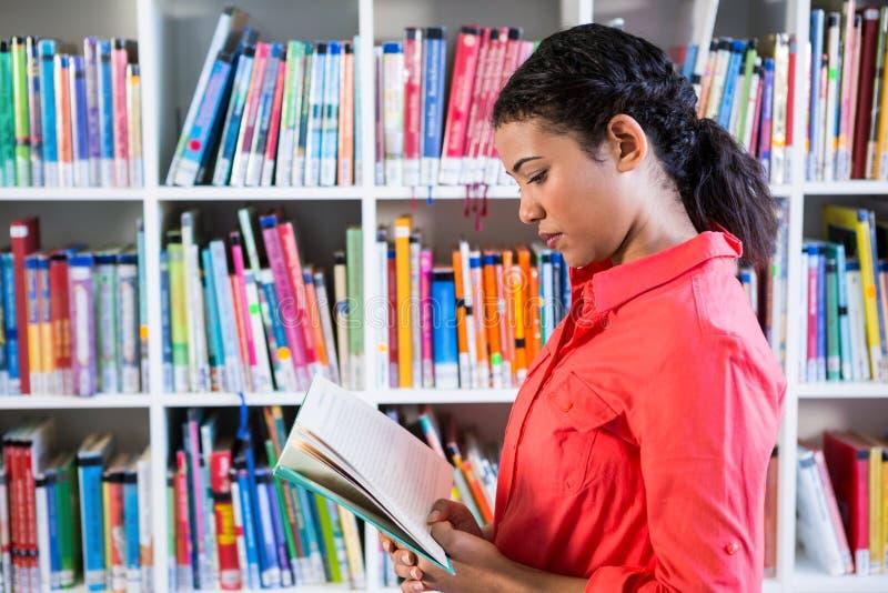 Livre de lecture de professeur à la bibliothèque à l'école photos stock