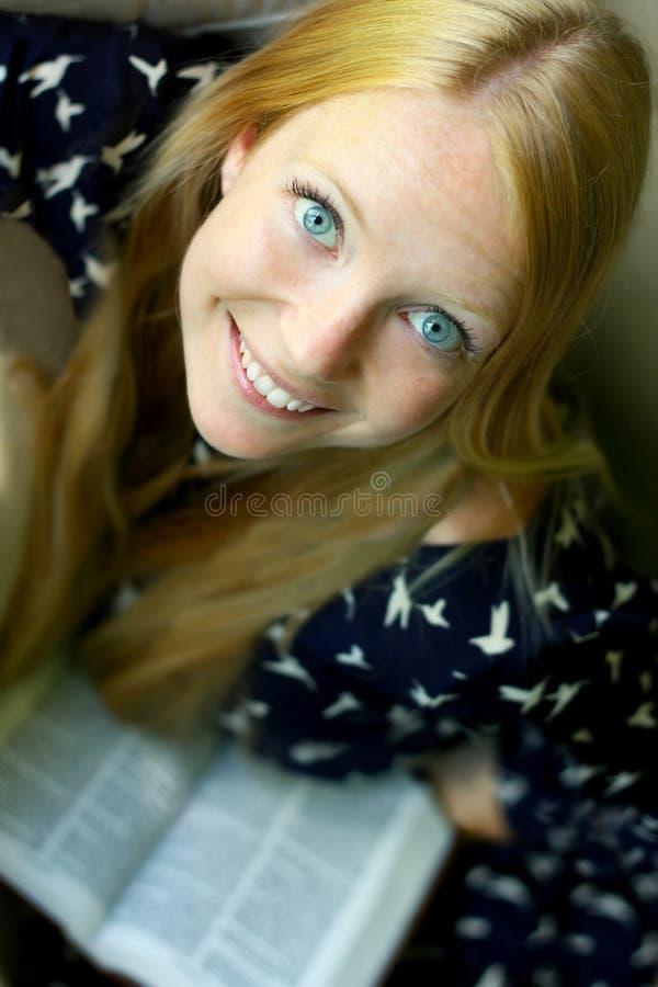 Livre de lecture de sourire de femme photographie stock