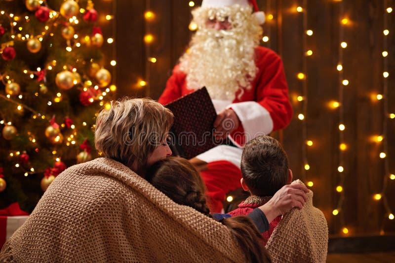 Livre de lecture du Père Noël pour la famille Mère et enfants assis à l'intérieur près d'un xmas orné de lumières - Joyeux Noël e photo libre de droits