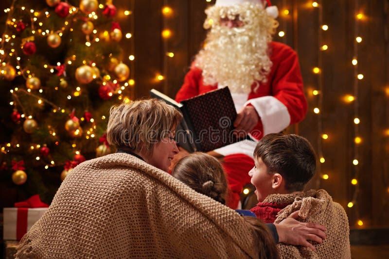 Livre de lecture du Père Noël pour la famille Mère et enfants assis à l'intérieur près d'un xmas orné de lumières - Joyeux Noël e image stock