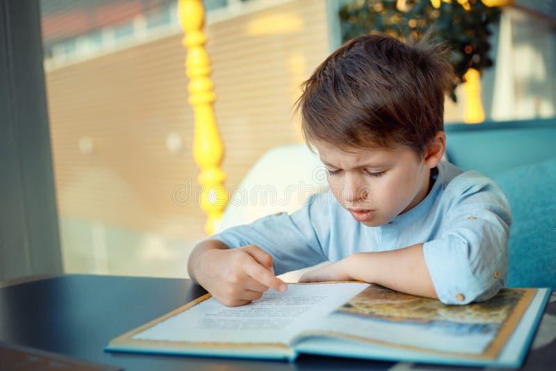 Livre de lecture ennuyeux et fatigué de petit garçon photographie stock libre de droits