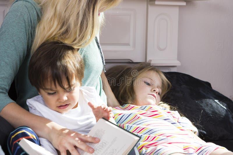 Download Livre De Lecture Fatigué De Mère Aux Enfants Photo stock - Image du sommeil, verticale: 77150560