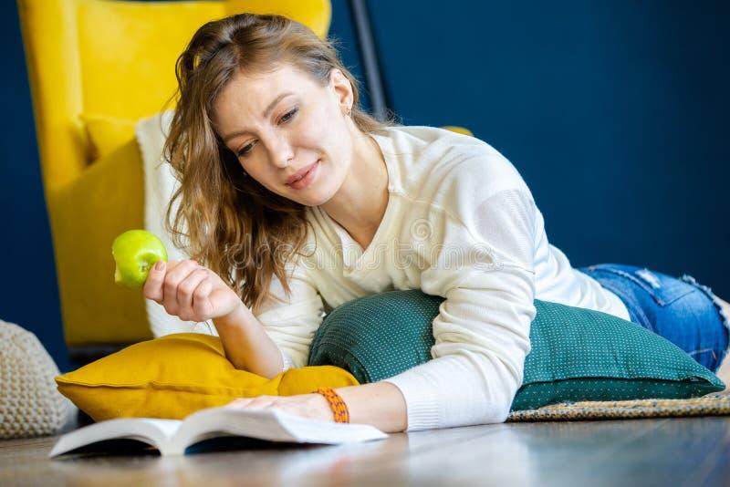 Livre de lecture de femme à la maison et s'étendant sur le plancher à côté du fauteuil jaune photo stock