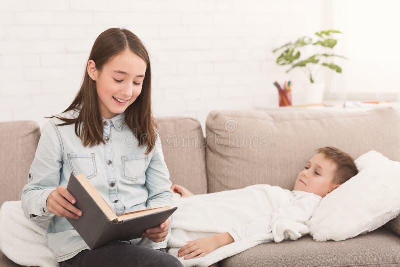 Livre de lecture de fille à peu de frère malade photographie stock
