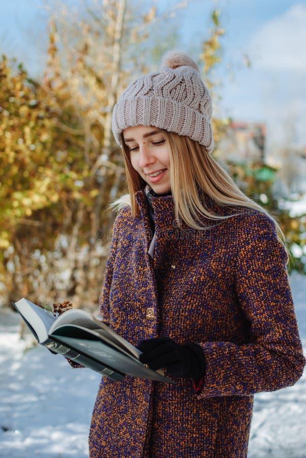 Livre de lecture de fille dehors en hiver image libre de droits