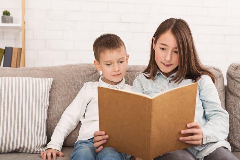 Livre de lecture de frère et de soeur sur le sofa photos libres de droits