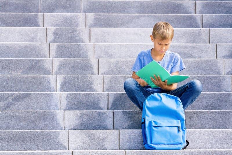 Livre de lecture de garçon se reposant sur les escaliers dehors image stock
