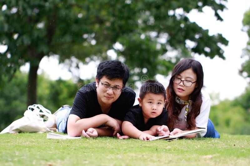 Livre de lecture heureux de famille de latino image libre de droits