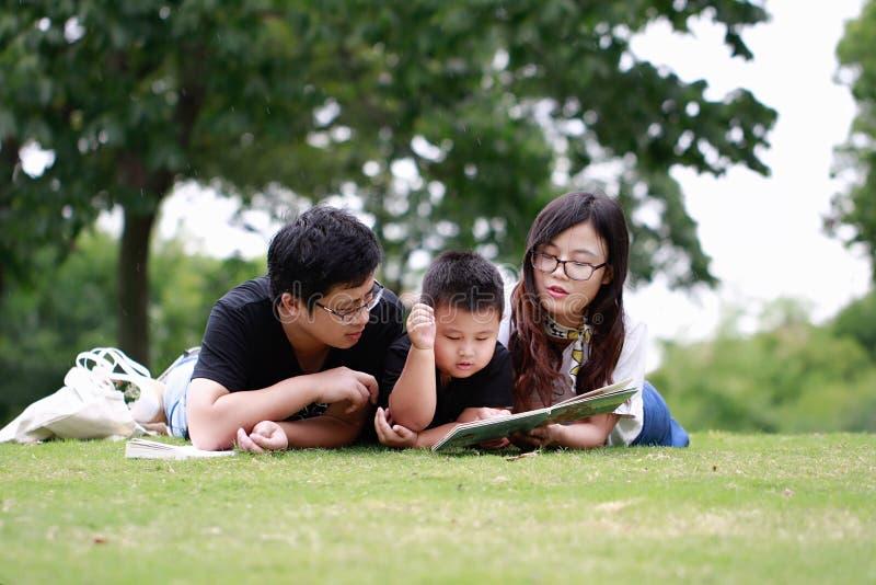 Livre de lecture heureux de famille de latino photo stock