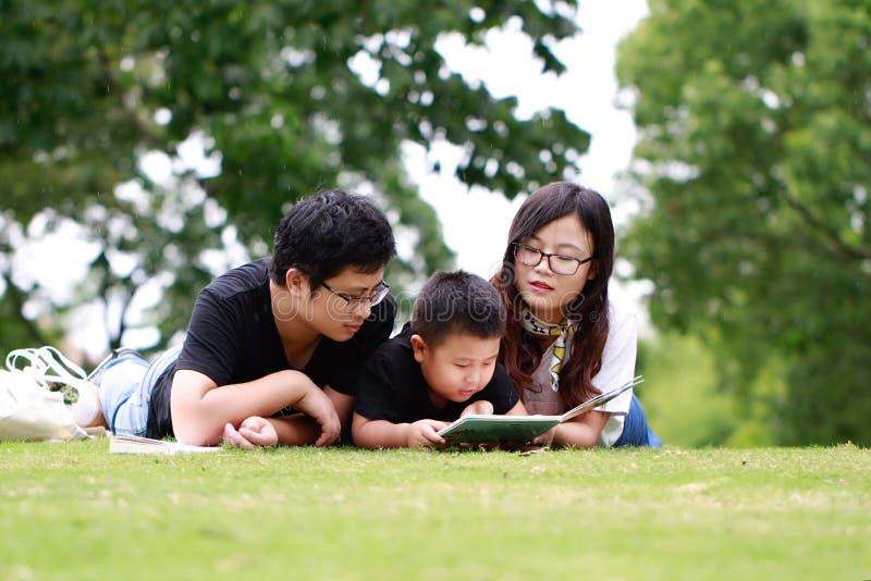 Livre de lecture heureux de famille de latino photo libre de droits