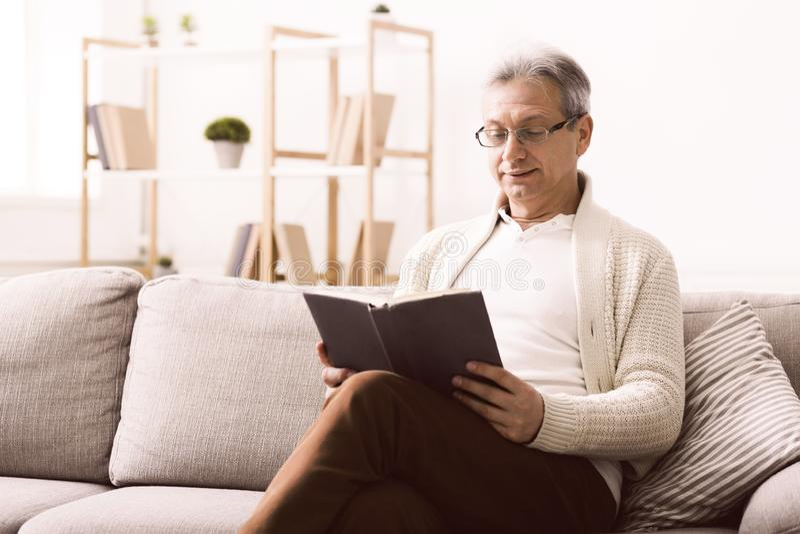 Livre de lecture heureux de retraité, ayant le repos sur le sofa photos libres de droits