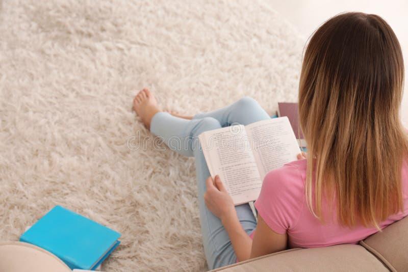 Livre de lecture de jeune femme sur le plancher à la maison images libres de droits