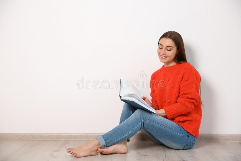 Livre de lecture de jeune femme sur le plancher près du mur photos libres de droits