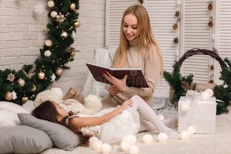 Livre de lecture de mère à sa petite fille près d'arbre de Noël photo libre de droits