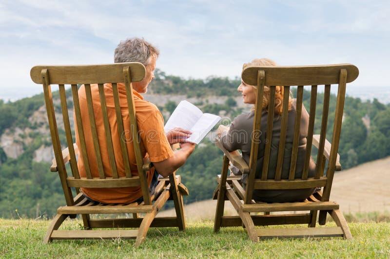Livre de lecture mûr de couples image stock
