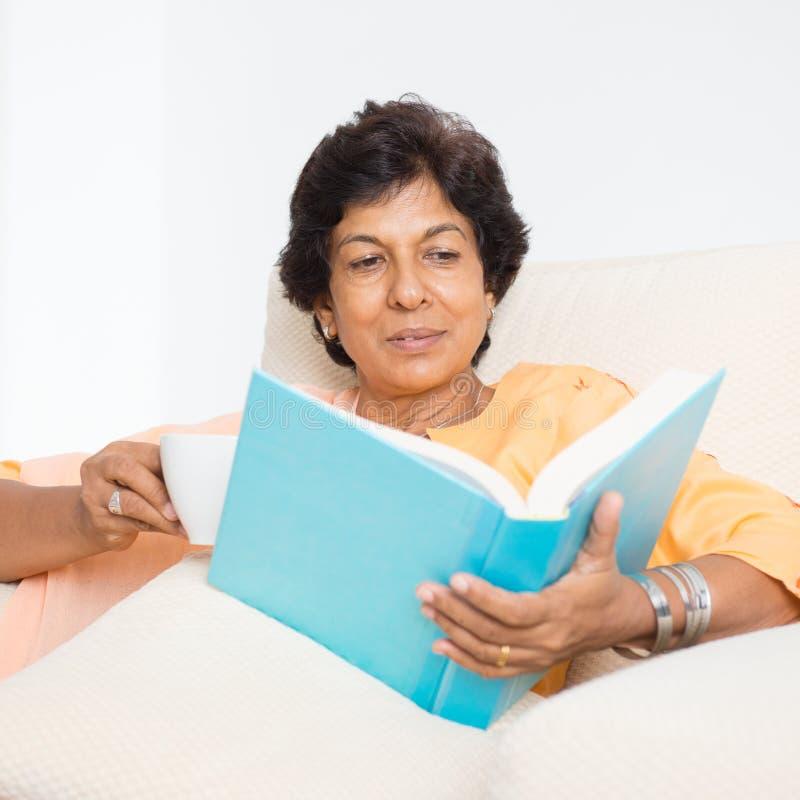 Livre de lecture mûr indien de femme photographie stock libre de droits
