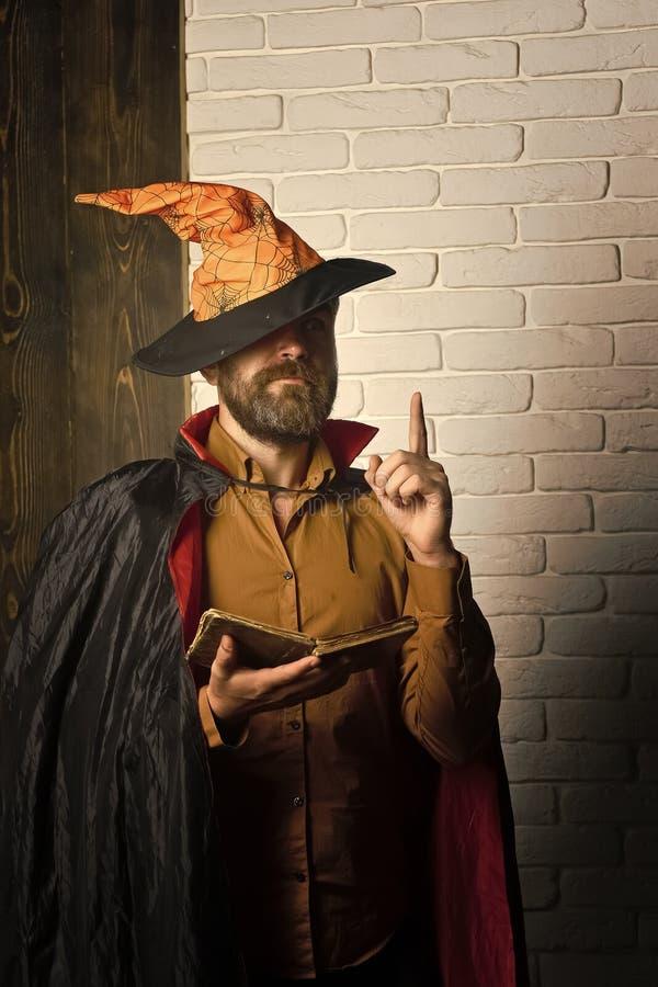 Livre de lecture de magicien de Halloween sur le mur de briques image stock