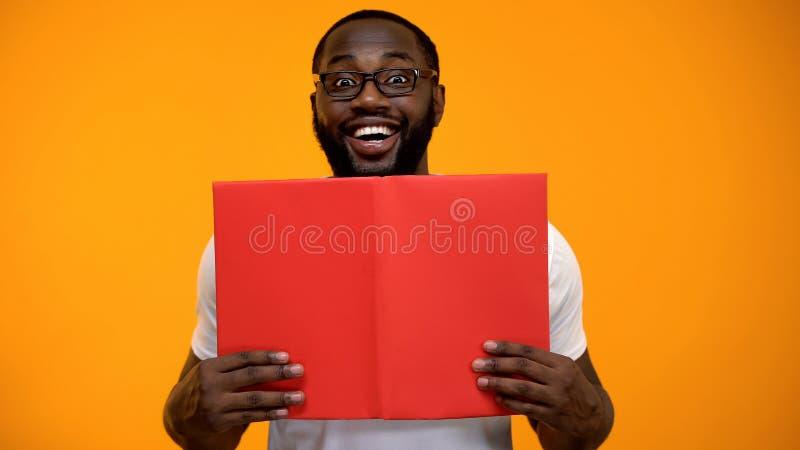 Livre de lecture masculin afro-am?ricain de sourire, ?tudiant et autod?veloppement, plan rapproch? photographie stock