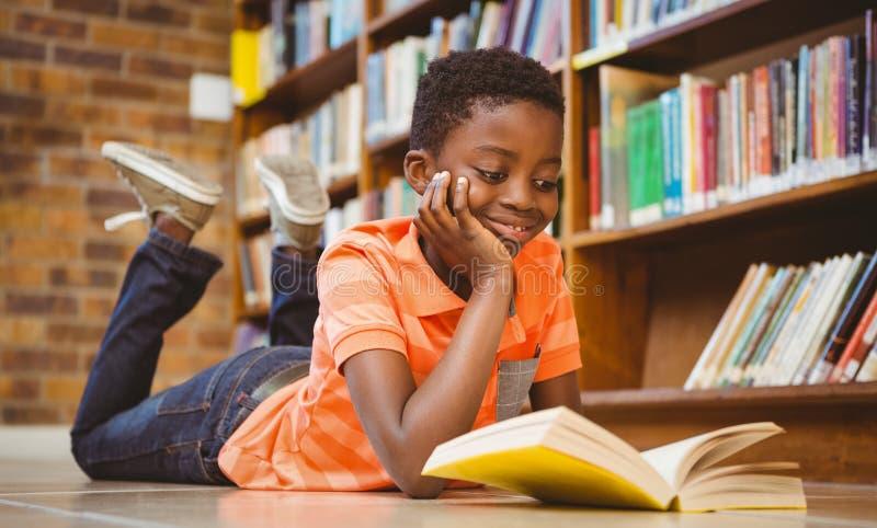 Livre de lecture mignon de garçon dans la bibliothèque photo libre de droits