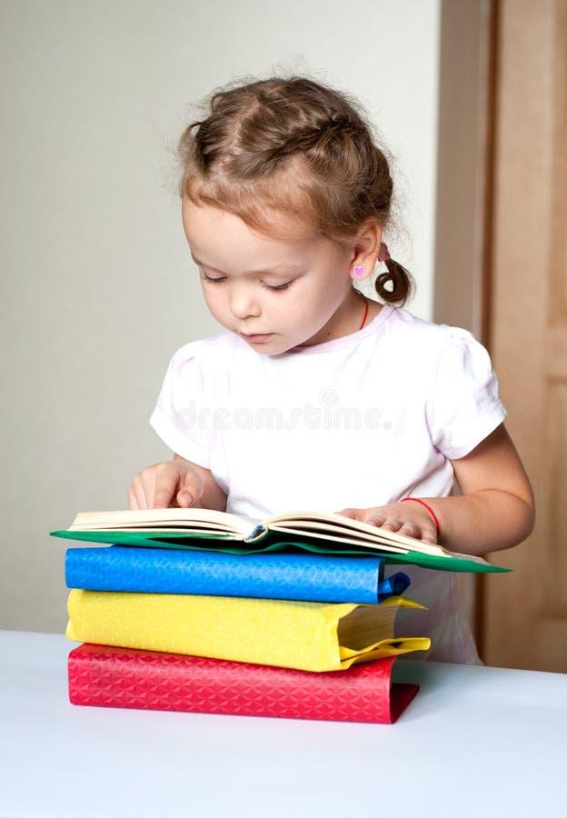 Livre de lecture mignon de petite fille photographie stock libre de droits