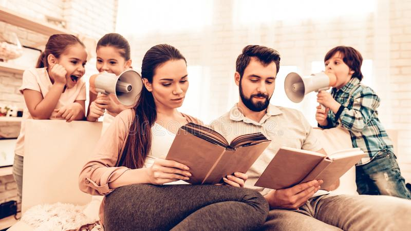 Livre de lecture mignon heureux de parents tandis que jeu d'enfants photo libre de droits