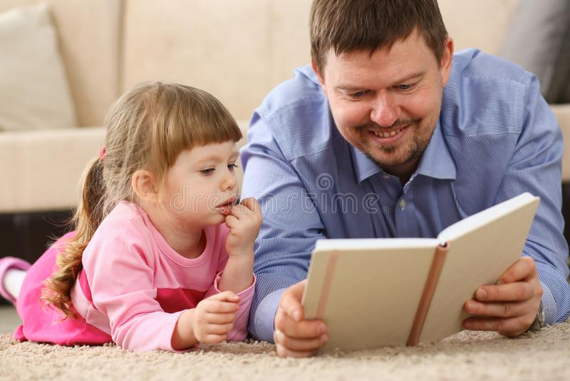 Livre de lecture de père de fille se trouvant sur le tapis images libres de droits
