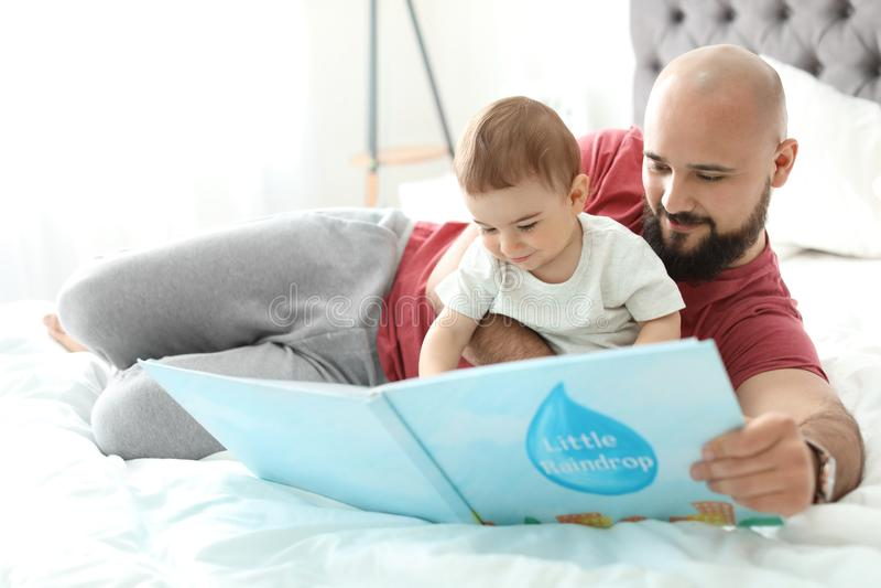 Livre de lecture de papa avec son petit fils images stock