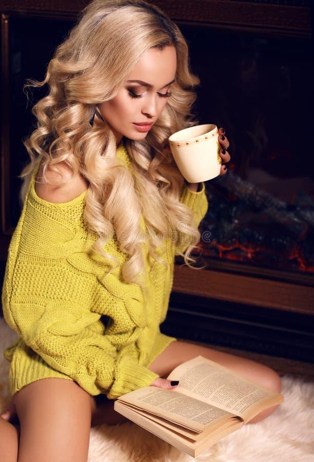 Livre de lecture sexy de femme et thé potable près d'une cheminée photo stock