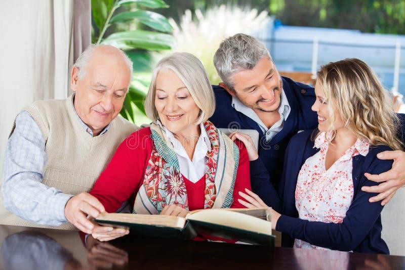Livre de lecture supérieur heureux de couples avec photographie stock