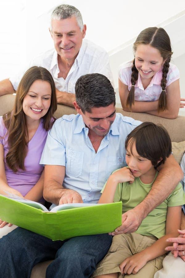 Livre de lecture sur plusieurs générations de famille photos stock