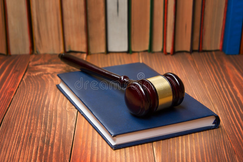 Livre de loi avec le marteau en bois de juges sur la table dans une salle d'audience ou un bureau de police photos libres de droits