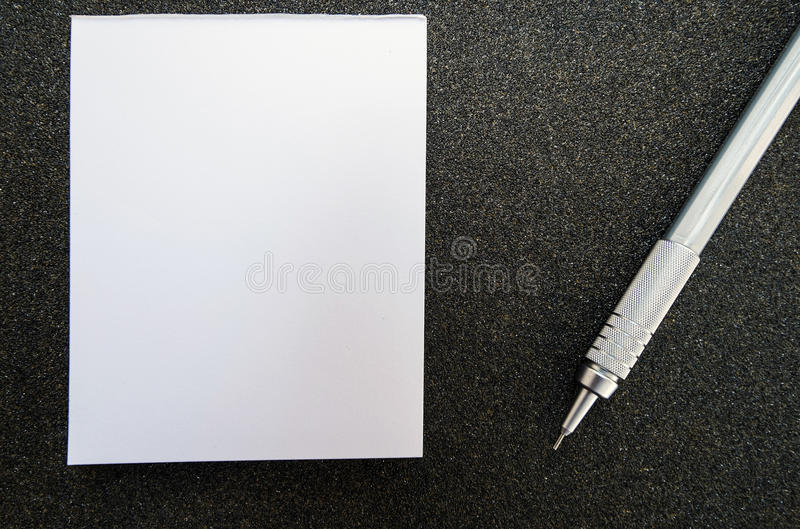Livre de papier de post-it vide avec le crayon, sur la texture noire de papier sablé photographie stock libre de droits
