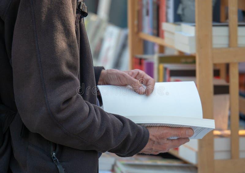 Livre de poche de lecture d'homme à une librairie photo stock