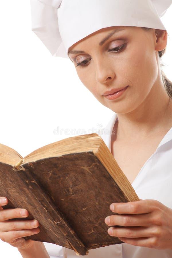 Livre de recettes de lecture de cuisinière de femme image stock