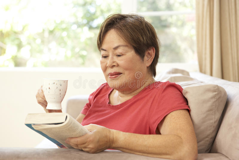 Livre de relevé aîné de femme avec la boisson à la maison images stock