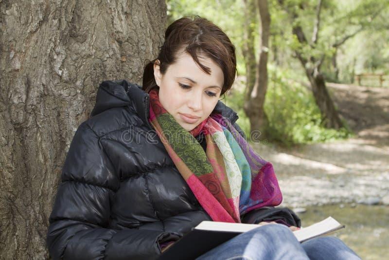 Livre de relevé de fille par un arbre photographie stock