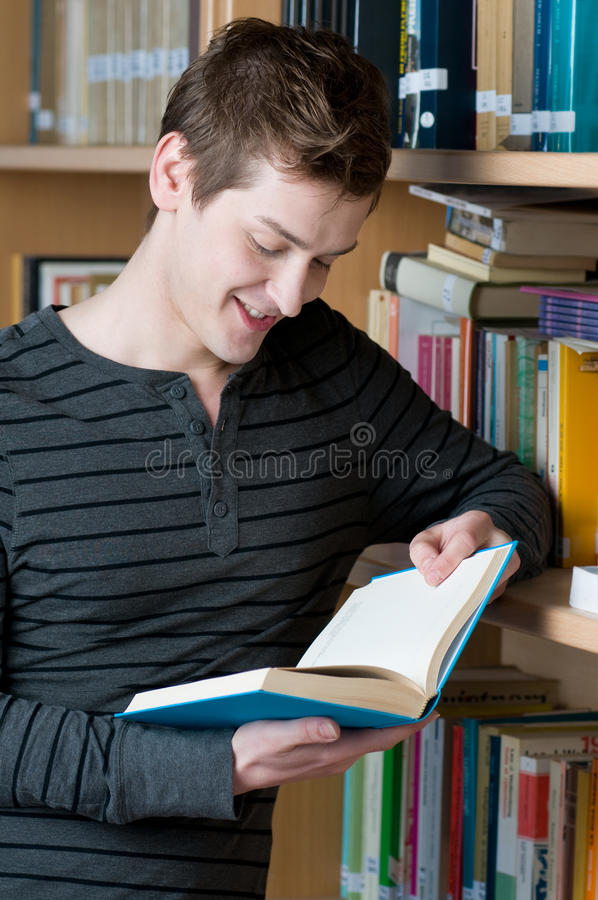 Livre de relevé heureux d'étudiant dans une bibliothèque photographie stock