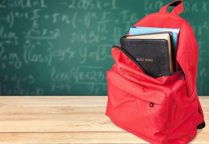 Livre de Sainte Bible dans le sac à dos d'école image stock