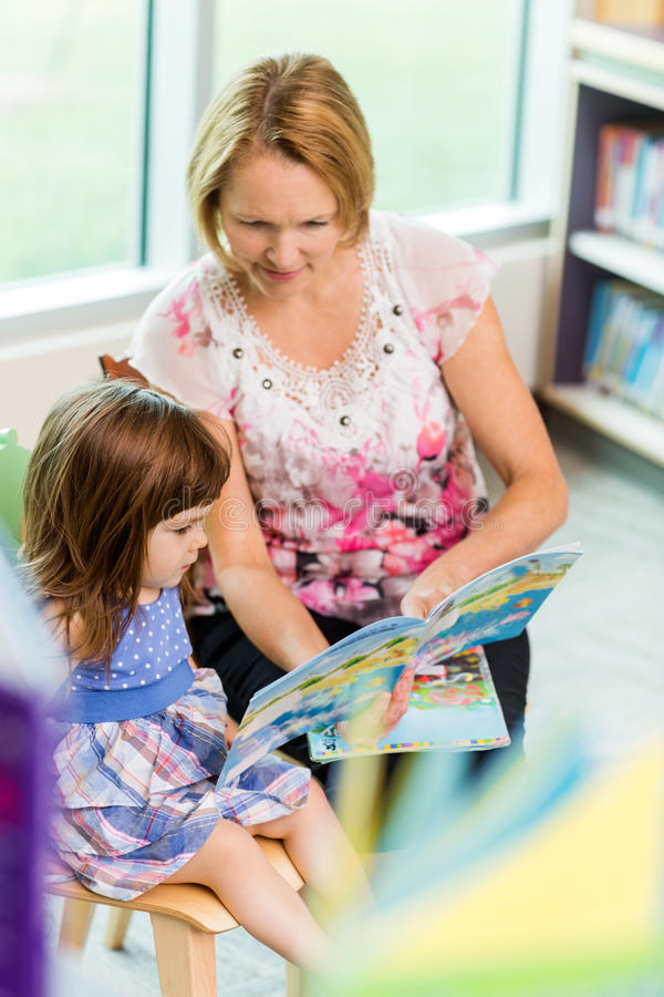 Livre de With Schoolgirl Reading de professeur photo stock