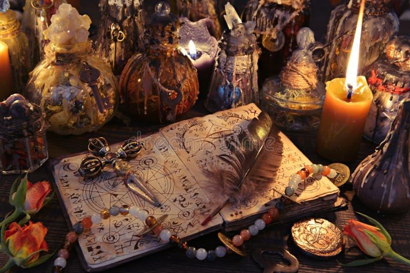 Livre de sorcière avec la croix, la cannette, les bougies brûlantes et les bouteilles magiques sur la table photographie stock