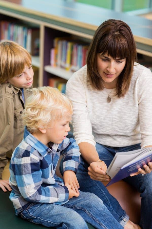 Livre de With Students Reading de professeur dans la bibliothèque photos libres de droits