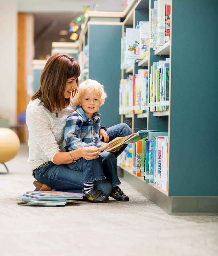 Livre de With Teacher Reading d'étudiant dans la bibliothèque photos libres de droits