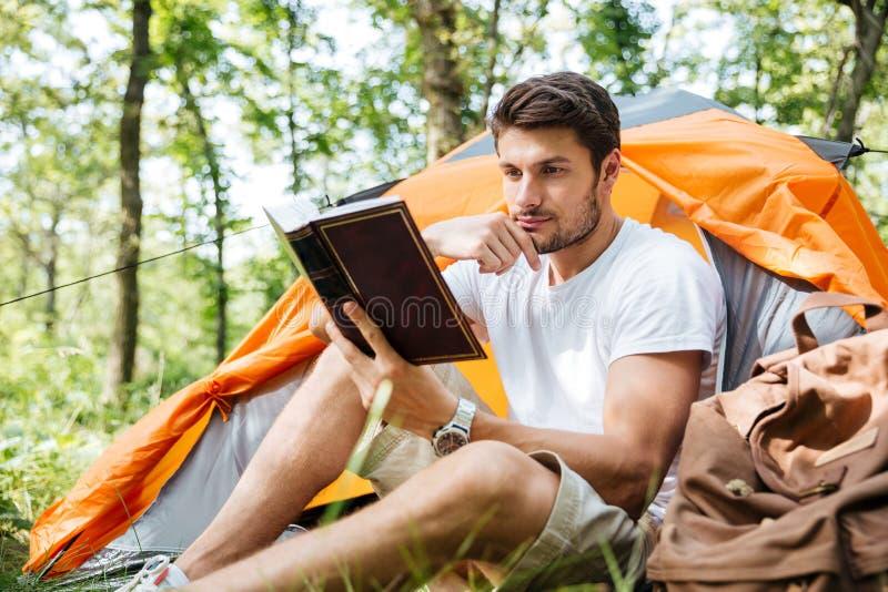 Livre de touristes de séance et de lecture de jeune homme réfléchi dans la forêt photos libres de droits