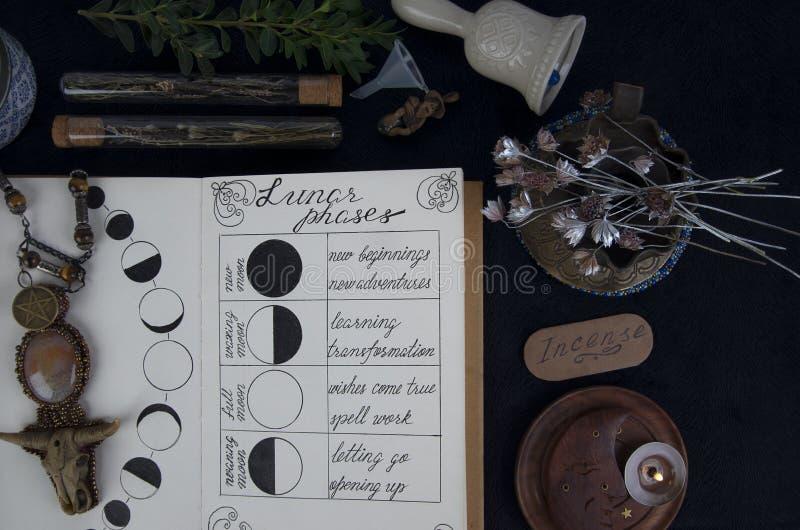 Livre des ombres avec des phases lunaires sur l'autel noir photos stock