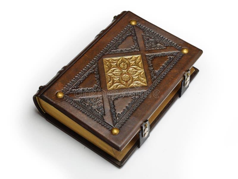 Livre en cuir antique avec le motif doré fixer à la table d'isolement photographie stock libre de droits