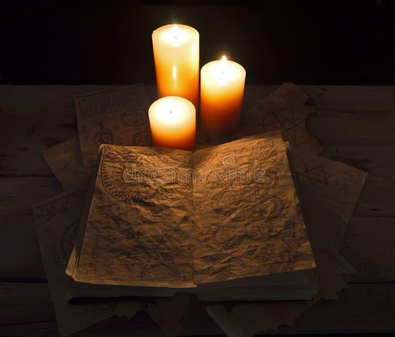 Livre et bougies de Grimoire photo stock