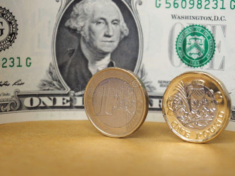 1 livre et 1 euro monnaie, et un billet du dollar au-dessus de fond en métal photo libre de droits