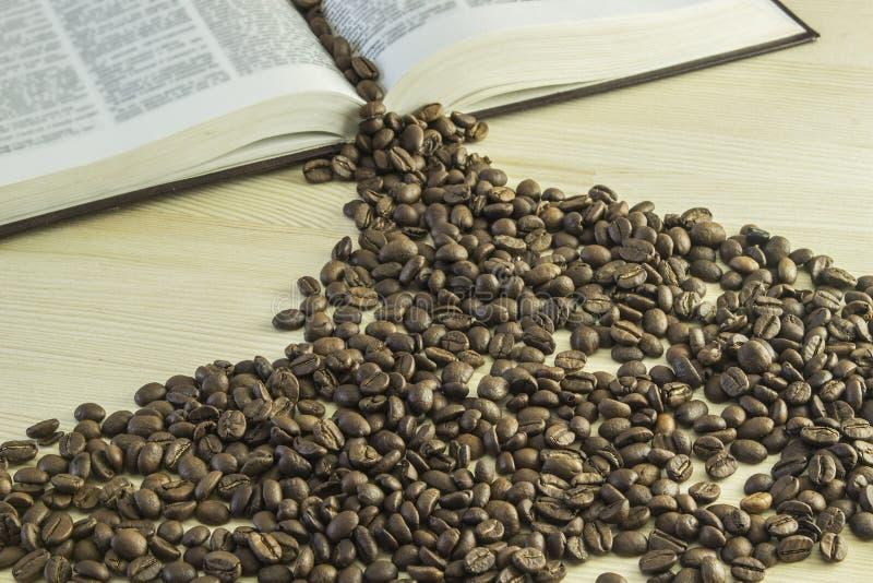 Livre et grains de café sur une table en bois photo stock