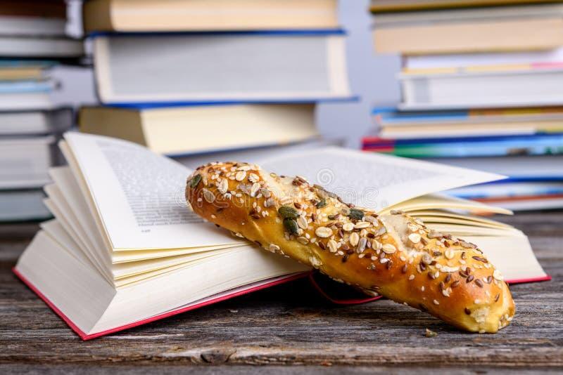 Livre et petit pain à grains entiers devant des piles de livres différents image libre de droits